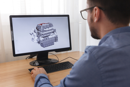 Engineer, Constructor, Designer in Glasses Working on a Personal Computer. He is Creating, Designinga New 3D Model of Car Engine, Motor in CAD Program. Freelance Work. Stock Photo