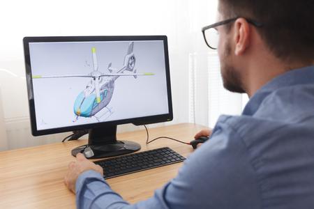 Ingeniero, constructor, diseñador de gafas trabajando en una computadora personal. Está creando y diseñando un nuevo modelo 3D de helicóptero en el programa CAD. Trabajo independiente. Foto de archivo