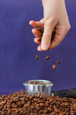 Female Hand Pouring the Coffee Beans into the Coffee Tamper on the Violet Background