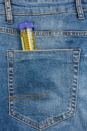 Close Up View to Test Tube Sticking Out From a Blue Jeans Pocket.