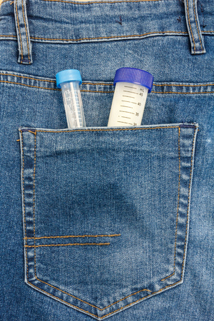 Close Up View to Test Tube With Sample of Sperm Sticking Out From a Blue Jeans Pocket. Imagens