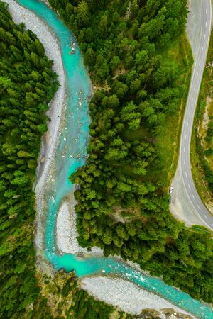 Inn River flowing in the forest in Switzerland. Aerial view from drone on a blue river in the mountains.