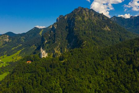 Aerial view on Neuschwanstein Castle Schwangau, Bavaria, Germany. Drone picture of Alps landscape with trees and mountains Standard-Bild