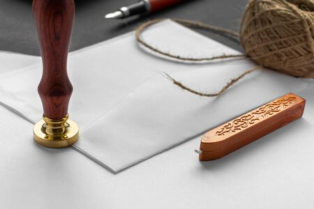 Notary public wax stamper. White envelope with brown wax seal, golden stamp. Responsive design mockup, flat lay. Still life with postal accessories Imagens