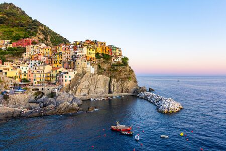 Panorama of Manarola in Cinque Terre, La Spezia. Colorful buildings near the ligurian sea. View on boats moored in marina with blue water at sunset