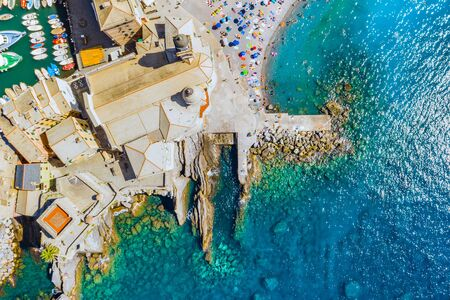 Aerial view of Camogli. Castle della Dragonara near the ligurian sea beach. View from above on rock and sea with transparent turquoise clean water and stones at the bottom.