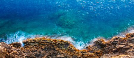 Aerial view of sea waves and rocky coast with turquoise and sapphire clear water. Long exposure.