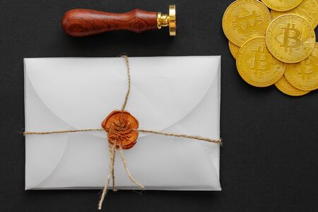 The designed envelope with a golden stamp is used for sending golden bitcoin coins as a gift. There are big golden BTC cryptocurrency coins in transparent envelope with golden stamp on the table