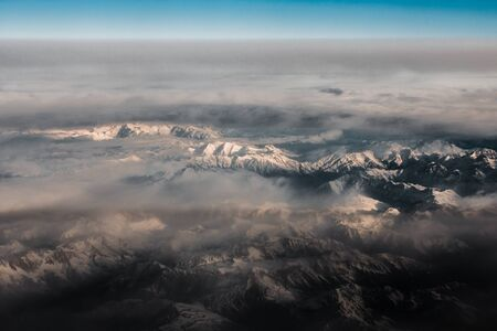 Aerial view from the plane on the panorama of the Alp mountains and hills ridge. Mountain peak of rocks covered by clouds and fog. View from above on mountain landscape