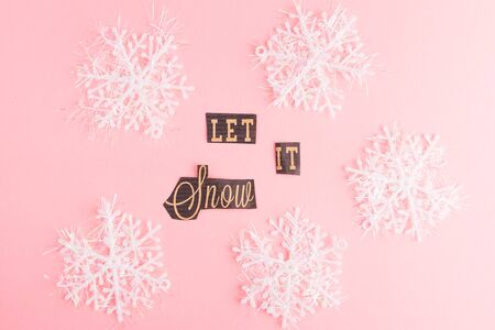 Snowflakes on a pink background with Let It Snow lettering inscription. Winter Holiday festive greeting gift card. Xmas flat lay concept Stock Photo