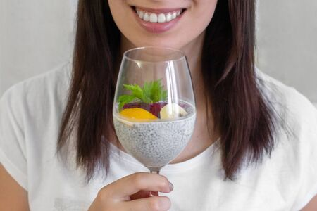 Young girl holding a glass of chia healthy food coconut pudding with banana, mango and dragon fruit in her hands. She is smiling. Healthy concept.