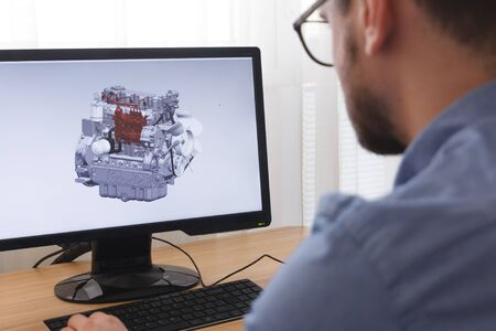 Engineer, Constructor, Designer in Glasses Working on a Personal Computer. He is Creating, Designinga New 3D Model of Car Engine, Motor in CAD Program. Freelance Work. Redakční