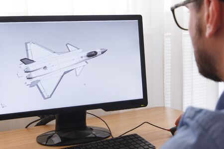 Engineer, Constructor, Designer in Glasses Working on a Personal Computer. He is Creating, Designing a New 3D Model of Aircraft, Airplane in CAD Program. Freelance Work, LOS ANGELES, CALIFORNIA - 25.10.2019