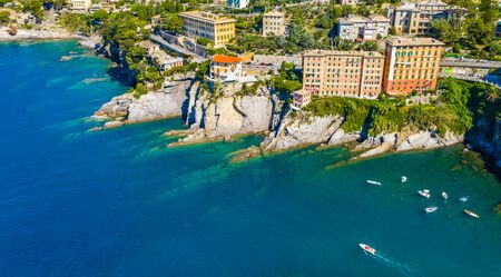 Aerial view of Camogli. Rock coast of Ligurian sea. View from above on boats and yachts. Panorama of the seaside with blue water in the summer time.