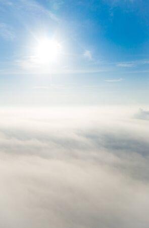 Luftbild über dem Nebel oder weißen Wolken mit strahlender Sonne. Schöner bewölkter Himmel des Sonnenaufgangs aus der Vogelperspektive. Über Wolken aus Flugzeugfenster oder Drohne. Standard-Bild