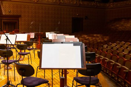 Music books and sheets with musical notation on the stands ready to the concert. Equipment of the Orchestra in philharmonia. 스톡 콘텐츠