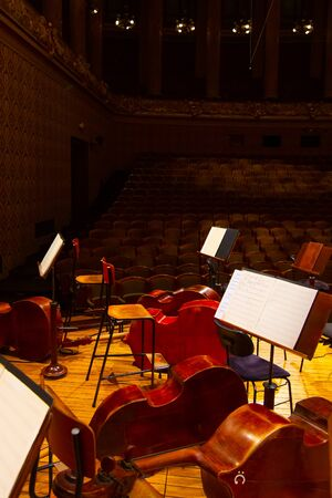 Music books and sheets with musical notation on the stands ready to the concert. Equipment of the Orchestra in philharmonia. Prague, 15.11.2019