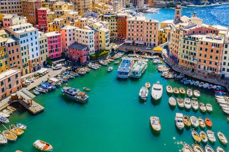 Aerial view of Camogli. Colorful buildings near the ligurian sea beach. View from above on boats and yachts moored in marina with green blue water
