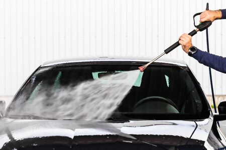A man is washing a car at self service car wash. High pressure vehicle washer machine clean with water. Car wash equipment.