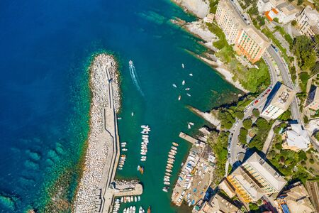 Camogli Harbor aerial view. Colorful buildings, boats and yachts moored in marina with green water