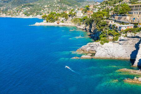 White boat sailing near rocky coast in Camogli, Italy. Aerial view on Adriatic seaside, liguria