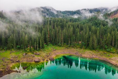 Aerial view of turquoise blue water of lake Carezza in Alps Dolomites. Lago di Karersee near fir tree forest Stock Photo