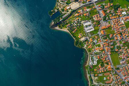 Vista aerea del lago di Como, Dongo, Italia. La costa è bagnata da acque turchesi blu.