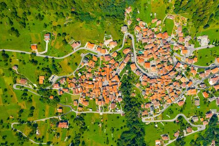 High angle view of houses with red roofs amoung trees on the top of the mountain in summer. Arial view on mountain Italian village 版權商用圖片 - 140260265
