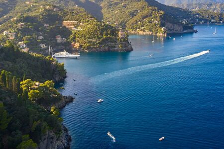 Yachts and boats are sailing in the Ligurian Sea on the mountain background, Portofino, Italy. Rocks and hills seaside with the traditional Italian houses on the top