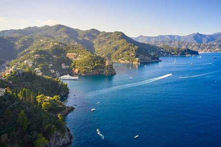 Yachts and boats are sailing in the Ligurian Sea on the mountain background, Portofino, Italy. Rocks and hills seaside with the traditional Italian houses on the top. Reklamní fotografie