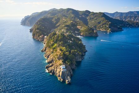 Arial view on the mountain range with a white lighthouse near Ligurian sea on the foreground. Tradition colorful italian houses are loceted on the top of the hill Reklamní fotografie