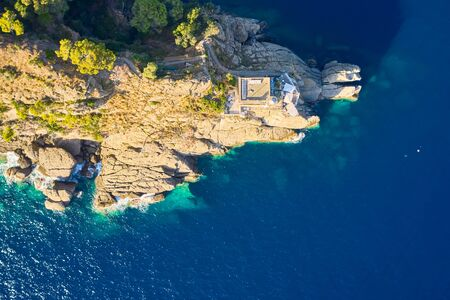Top view on a lighthouse standing on the rocky hill near the sea with blue turquoise water in Portofino, Italy. Ligurian sea washes a coast with the big stones Reklamní fotografie