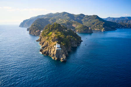 Arial view on the mountain range with a white lighthouse near Ligurian sea on the foreground. Tradition colorful italian houses are located on the top of the hill Reklamní fotografie