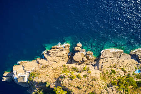 Top view on a lighthouse standing on the rocky hill near the sea with blue turquoise water in Portofino, Italy. Ligurian sea washes a coast with the big stones