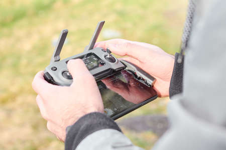 Close up mans hands holding drone remote controller with smartphone in the field. Concept of aerial shooting and flying, San Francisco, May 2020.