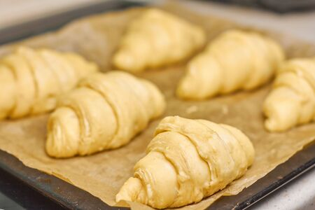 Unbaked raw croissants on a black tray with baking paper. Process of preparation of dessert from yeast dough. Concept of traditional french or italian pastry at home Фото со стока - 146386496