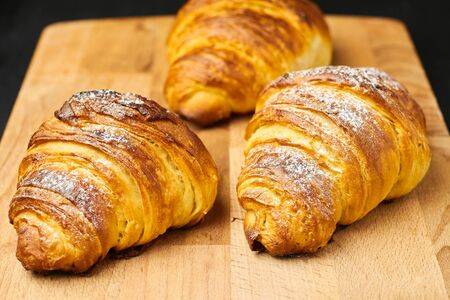 Close up three freshly baked croissants with sugar powder on a wooden desk. Puff french pastry. 免版税图像
