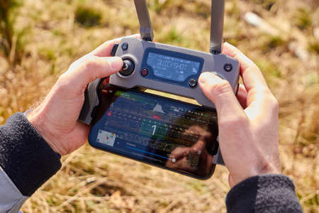 Close up mans hands holding drone remote controller with smartphone in the field. Concept of aerial shooting and flying, San Francisco, May 2020