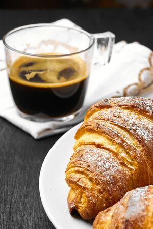 Buttery croissants and a cup of coffee on a black background. Homemade baking
