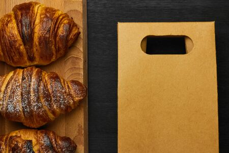 Delivery of croissant in a card bag with copy space on a black background. French or italian breakfast.