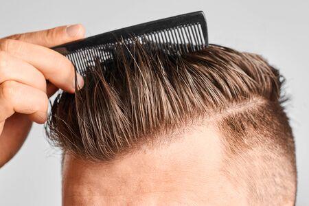 Mann, der sein sauberes Haar mit Plastikkamm kämmt. Haarstyling zu Hause. Konzept von Haarausfall oder Schuppen