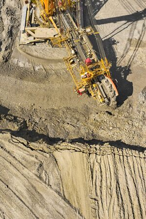 Huge bucket wheel excavator or mobile strip mining machine mining coal in a quarry. Heavy industry concept