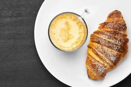Top view of cappuccino and croissant on a plate on a black background with copy space. Concept of a tasty breakfast. French or italian pastry. 免版税图像