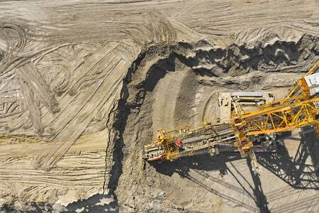 Aerial view of large heavy equipment machine mining natural resource. Coal mining by bucket wheel excavator. Heavy industry