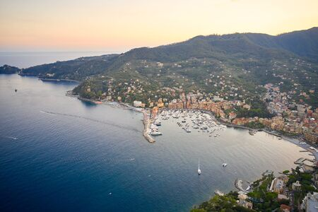 Aerial view of a marina with yachts and boats. Reflection of sun rays in the water Ligurian sea at the sunset in Santa Margherita Ligure near Portofino, Italy.