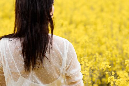 Young woman in a white dress standing in a rapeseed field. Blooming yellow flowers with copy space