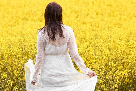 Young beautiful woman in a white dress dancing in a rapeseed field. Blooming yellow flowers in spring Foto de archivo
