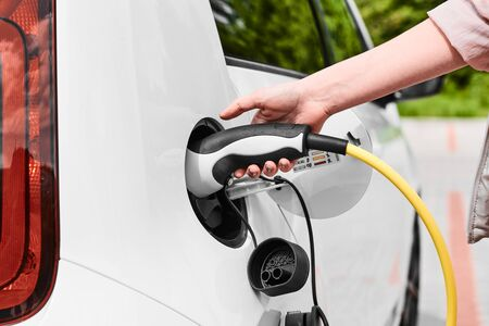 Woman unplugging a charger from an electric car socket. Eco friendly vehicle with zero emission Stock Photo