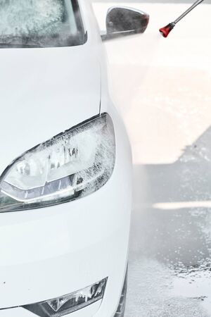 Closeup of a headlight of a white car under the water jet during the washing at high pressure car wash. Self wash concept. Фото со стока
