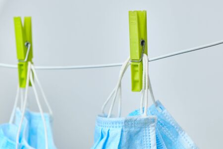 Drying of blue protective surgical masks on clothesline with green clothespins on a white background.Prevention of coronavirus spread.